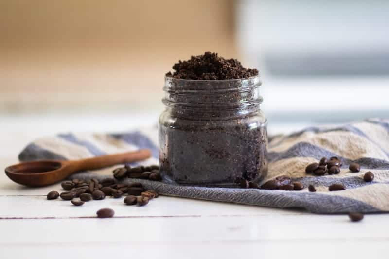 organic coffee scrub in mason jar with wooden measuring spoon coffee beans and a blue and white striped towl.