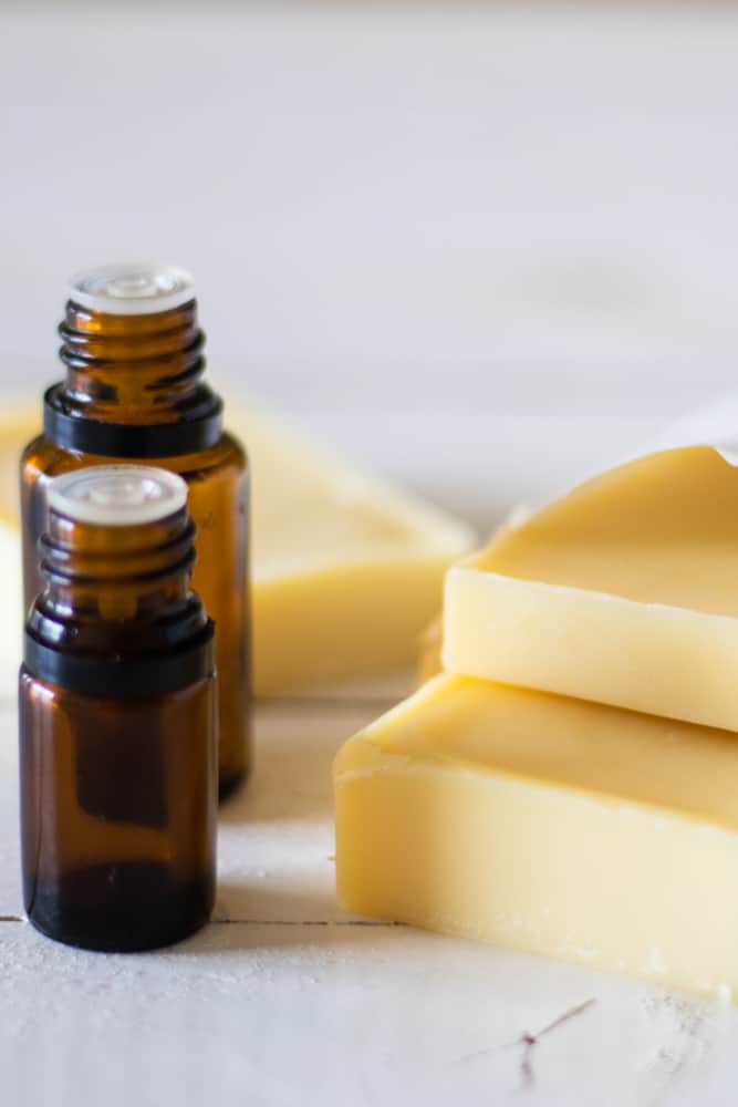 amber color essential oil bottles next to conditioner bars