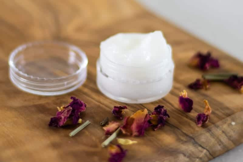 lid off of coconut oil eye cream in small container on wooden board with rose petals around it