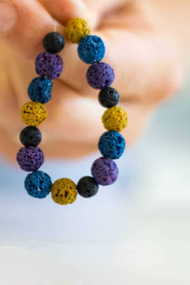 Holding multi-colored handmade diffuser bracelet
