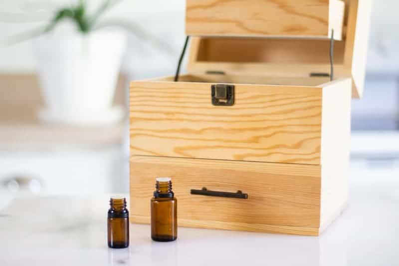 amber colored essential oil bottles in front of storage box on a white marble table top