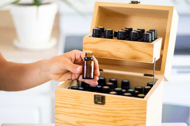 Taking essential oil bottle from wooden oil storage box