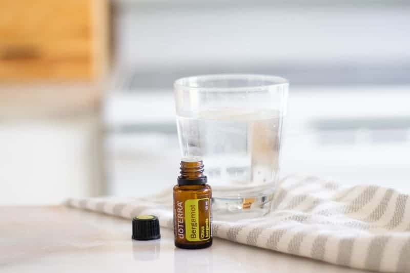 bergamot oil with the lid off in front of glass of a glass of water on a light colored towel