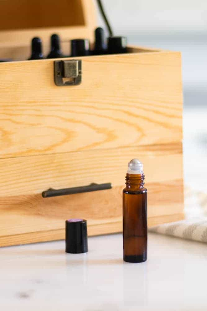 bergamot roller bottle for hair in front of custom wooden oil storage box