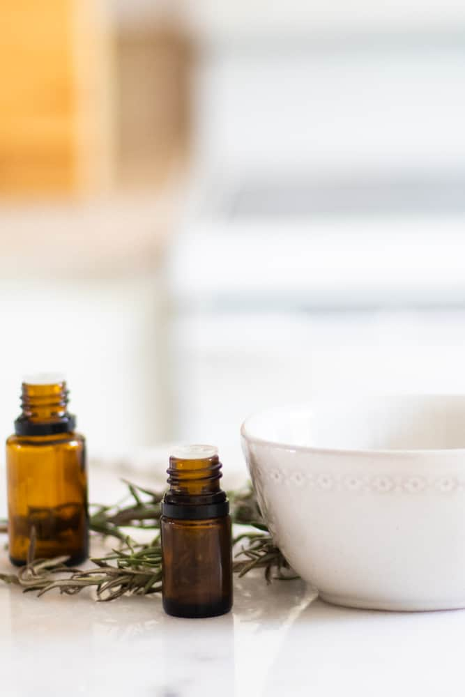 Diy deep conditioner ingredients with amber colored essential oil bottles, white bowl, and fresh rosemary on white marble