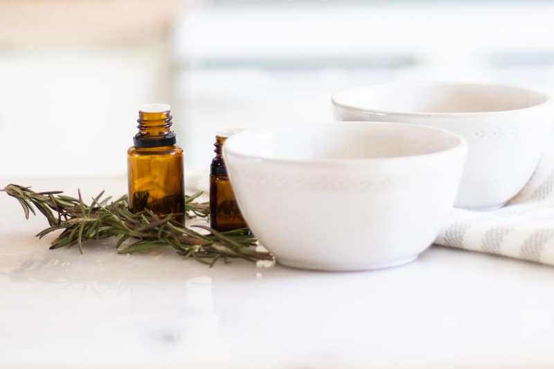 white bowls with fresh rosemary on marble table sitting on a white and grey towel