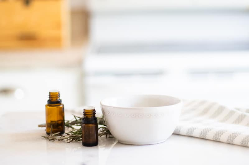 Homemade deep conditioner treatment in small white bowl on white table with amber oil bottles rosemary sprigs and a white and grey striped towel