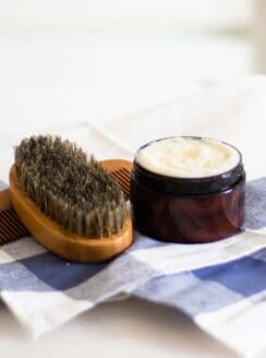 beard conditioner in amber colored container on blue checkered tea towel.