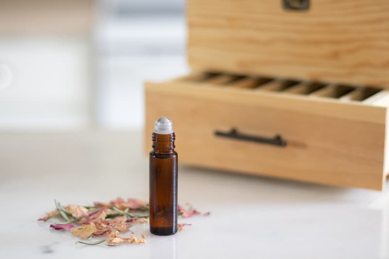 oils for acne in amber colored roller bottle in front of wooden box