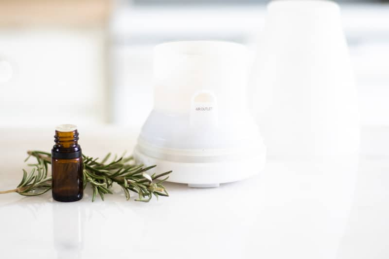 rosemary essential oil bottle and white diffuser