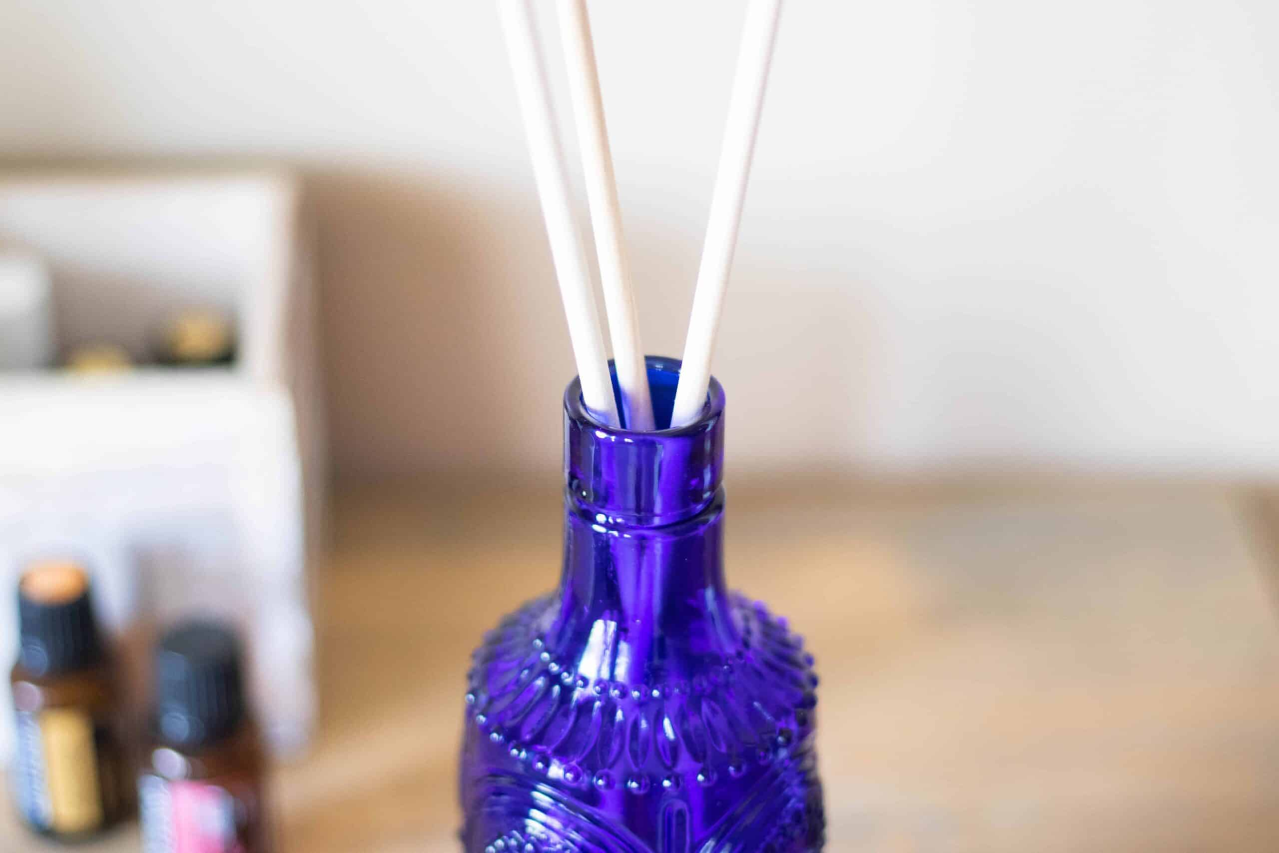 homemade reed diffuser in blue vase on corner table