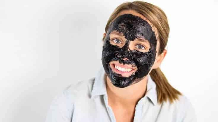 charcoal face mask on women's face