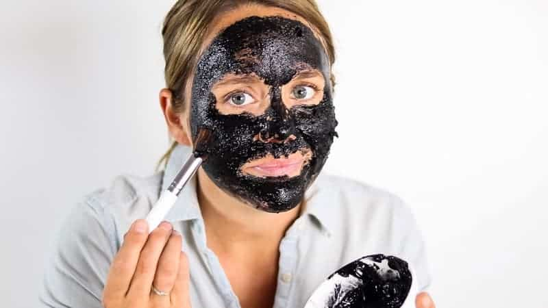 applying charcoal mask on face