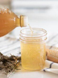 pouring apple cider vinegar into mason jar