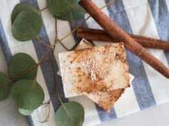 homemade cinnamon soap bar on white and blue tea towel