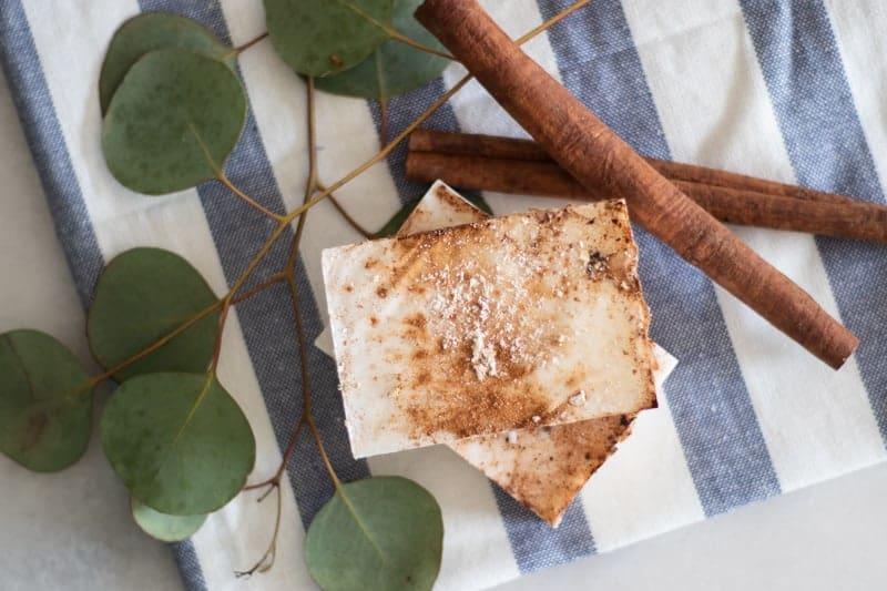 homemade cinnamon soap bar on white and blue tea towel