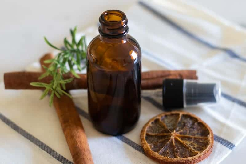 homemade men's cologne in amber color spray bottle with decorative dried spices.