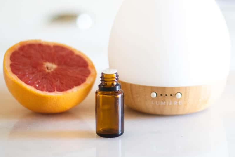 amber essential oil bottle in front of a grapefruit and a white diffuser