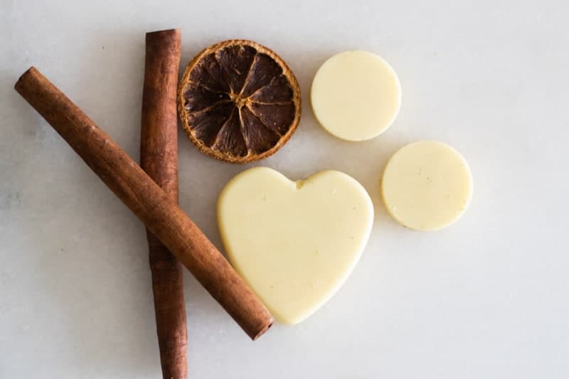 homemade wax air freshener hearts on white marble with cinnamon sticks and dried orange slice