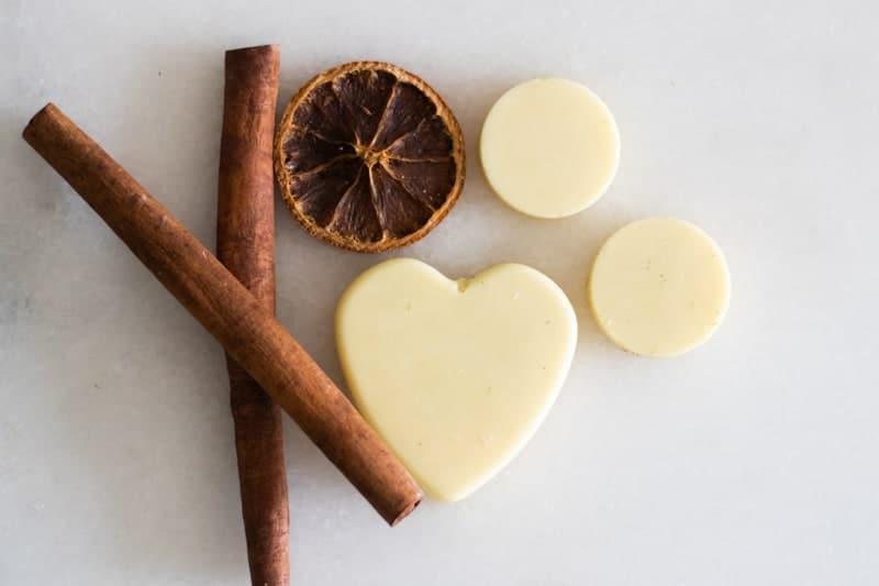 homemade wax air freshener hearts on white marble with cinnamon sticks and dried orange slice.