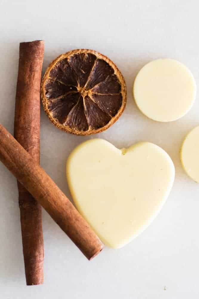 soy wax scented sachets on white marble with cinnamon sticks and orange slice
