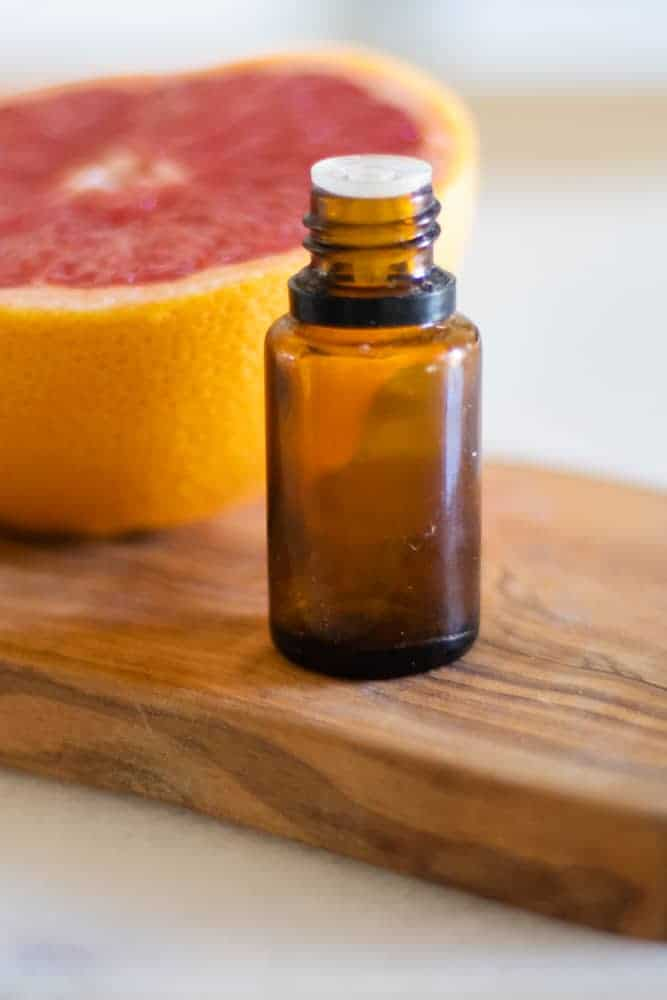 essential oil bottle in front of grapefruit