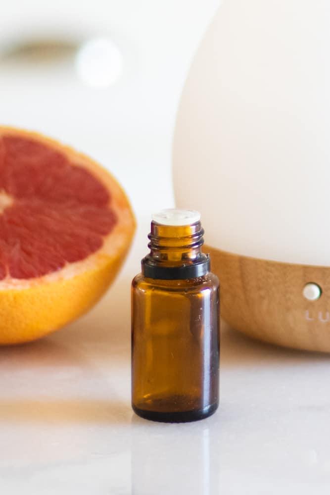 grapefruit essential oil bottle on white marble