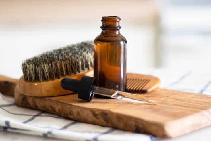 beard oil in a dropper bottle on wooden cutting board