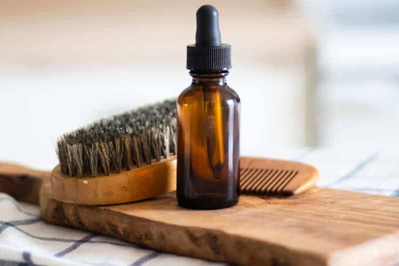 homemade beard oil in amber dropper bottle on wooden board