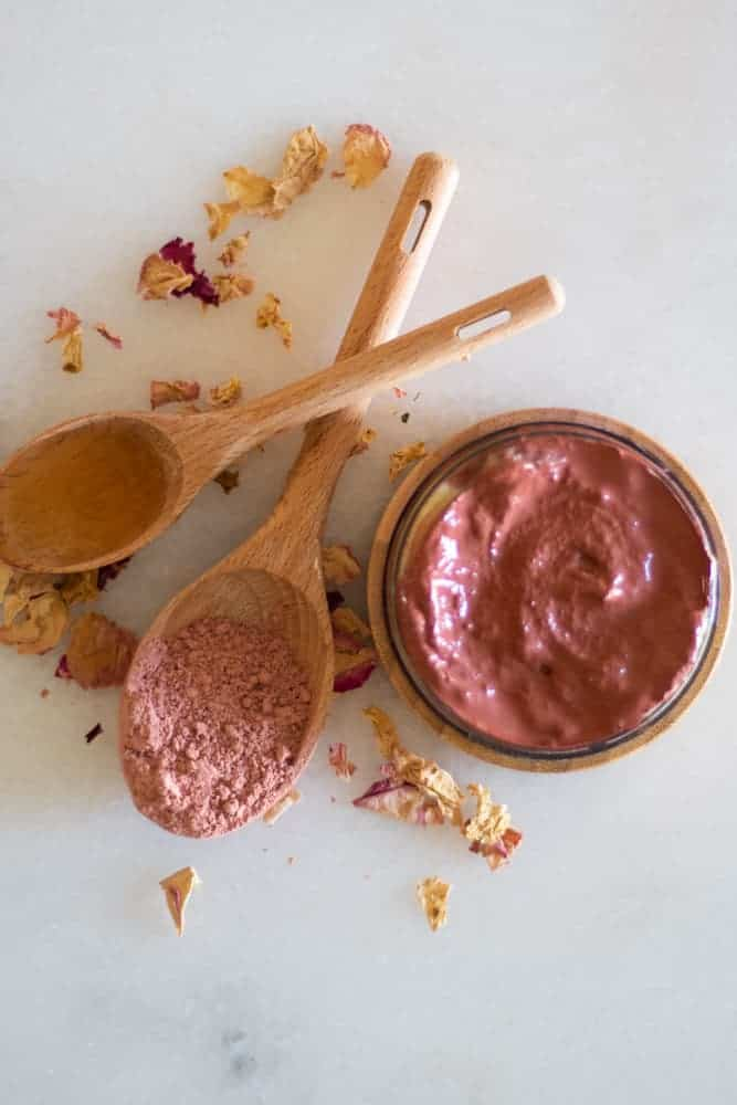 homemade rose clay face mask on white marble with rose petals and wooden spoon of rose clay