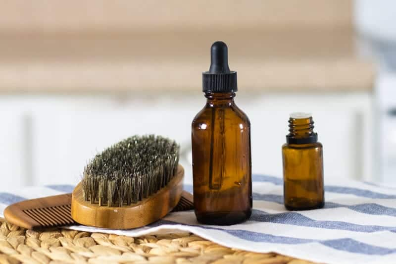 beard shampoo, amber colored essential oil bottle, and beard brush and comb on white and blue tea towel