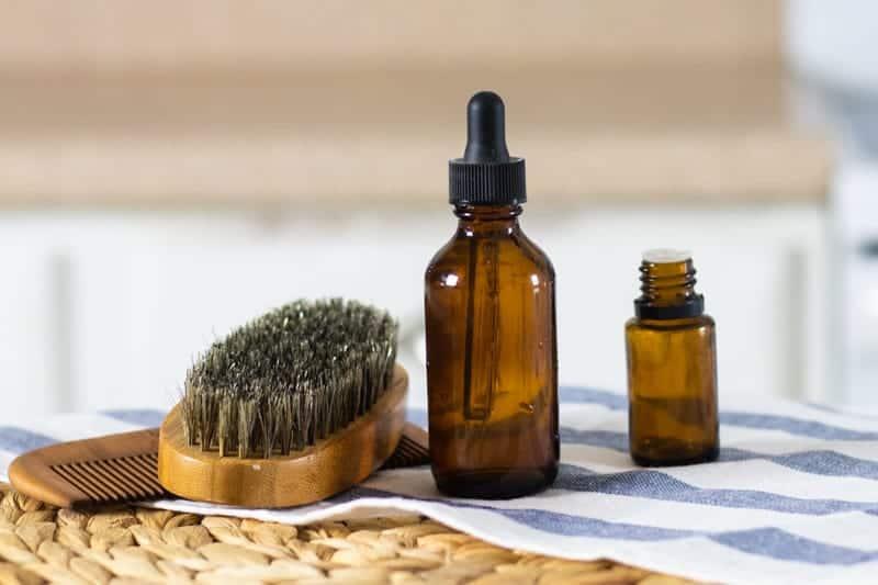 beard shampoo in amber dropper bottle on white and blue tea towel