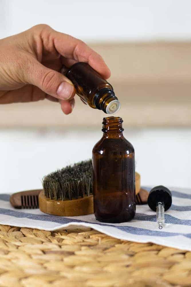women adding drops of essential oils to homemade beard shampoo
