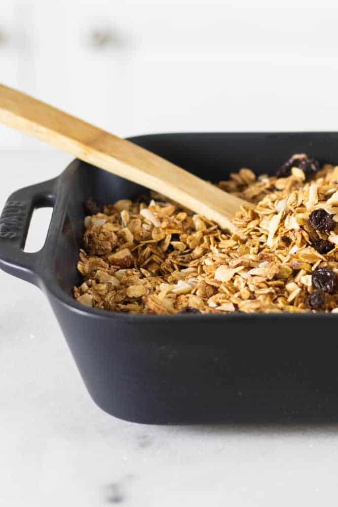 homemade granola in black baking dish with wooden spoon in it