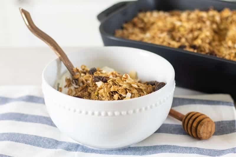 homemade sugar free granola in white bowl with yogurt