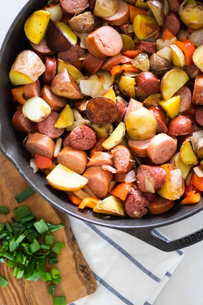 Crispy potatoes with chopped sausage links peppers and onions in a lodge skillet with a wooden cutting board of diced green onions.