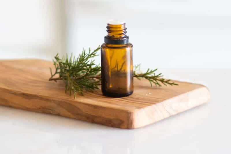 Siberian fir essential oil on wooden board with pine needles around it