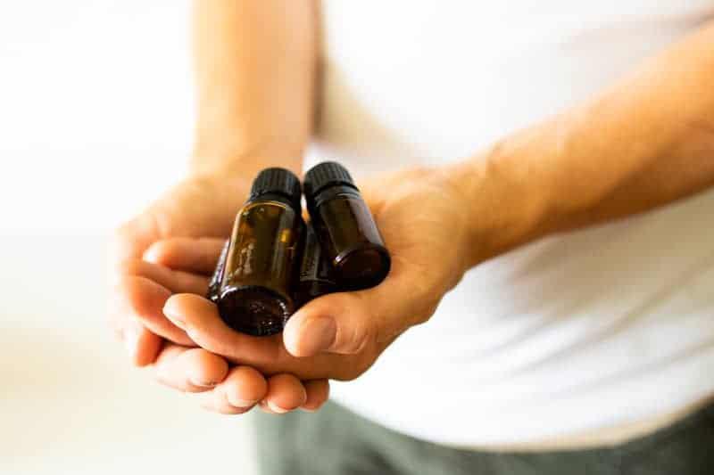 hand holding essential oil bottles