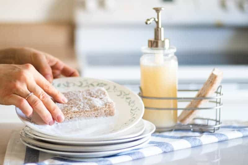 washing white plate with homemade dish soap