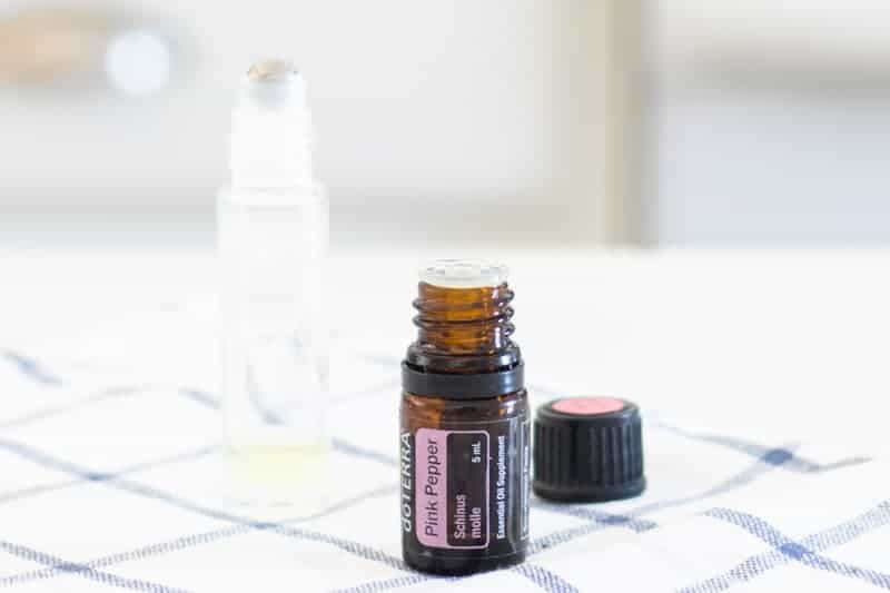 Bottle of pink pepper essential oil sitting on white and blue tea towel.