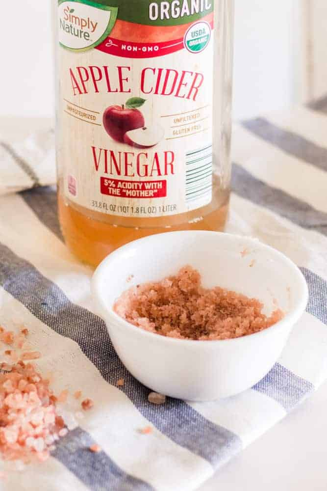 Pink salt scrub for dry scalp in a white bowl with apple cider vinegar.