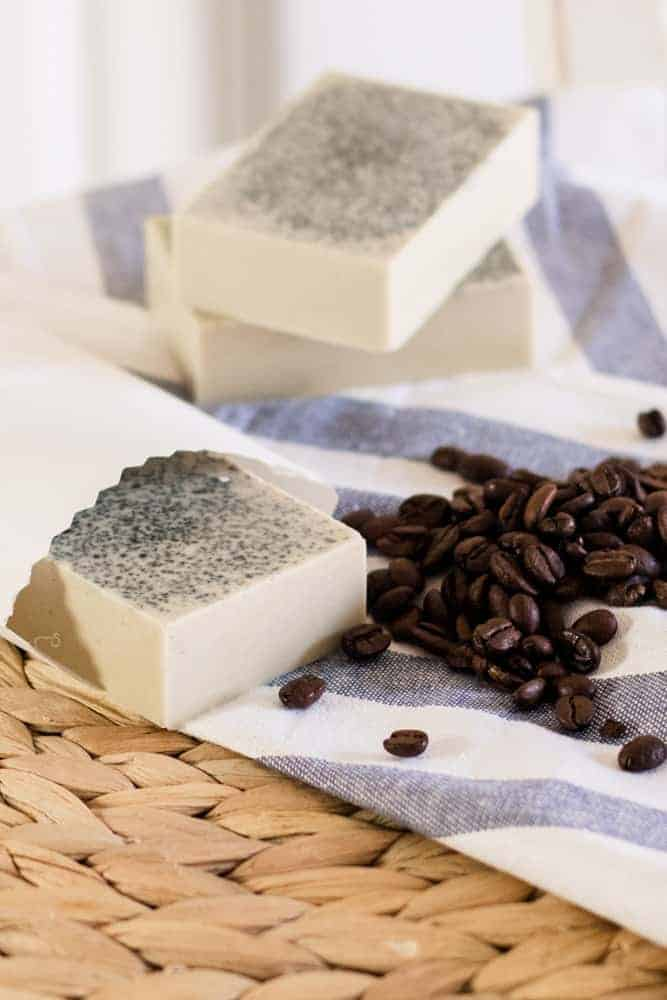 Goat milk coffee melt and pour soap bar in white paper and whole coffee beans around it.