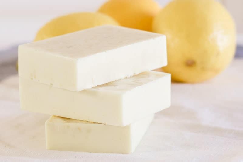 Lemon soap bars stacked on white tea towel with fresh lemons behind them.