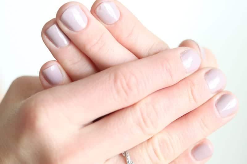 Women's hands with pink fingernail polish.