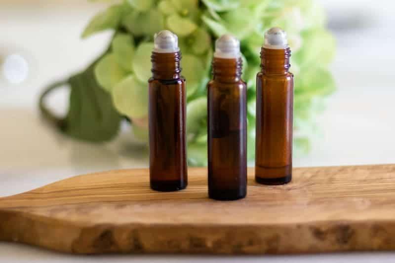 Essential oil roller bottles on wood cutting board.