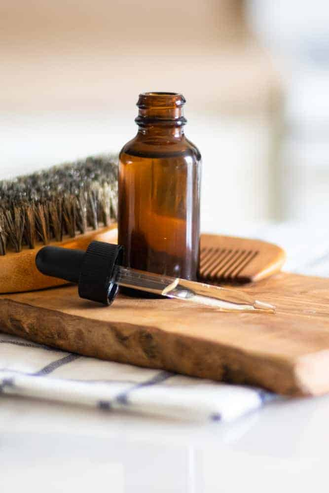 Dropper bottle with essential oils in it on wood board with bread brush and comb behind it.