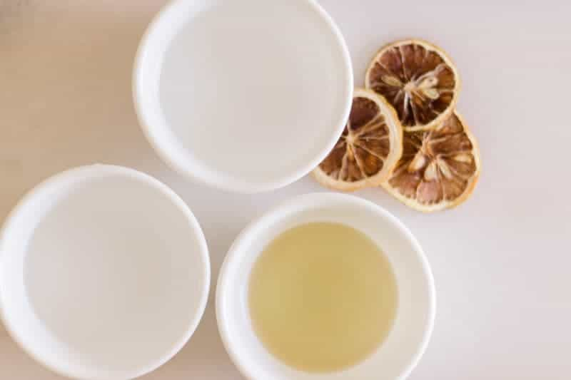 Three white bowls with water, vinegar, and olive oil in it.