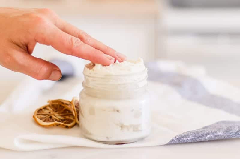 Women's hand in jar of homemade hand cream.