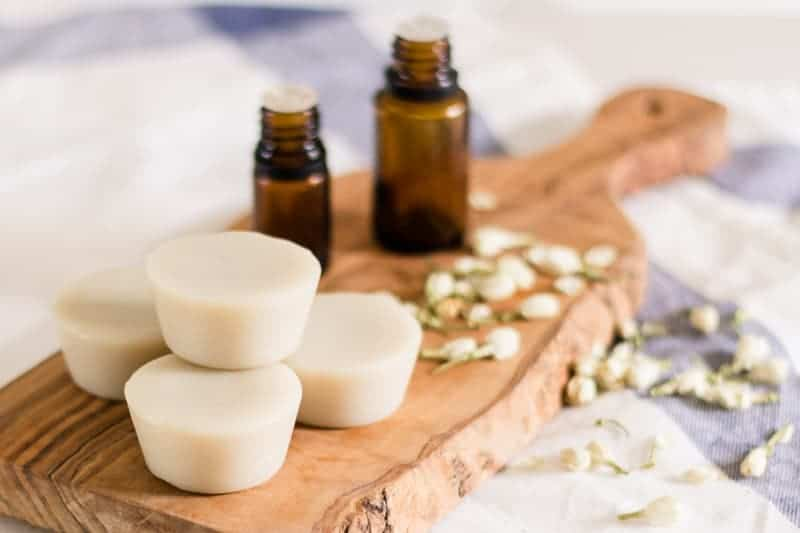 DIY lotion bars and essential oil bottles sitting on wood board with jasmine flowers around them.