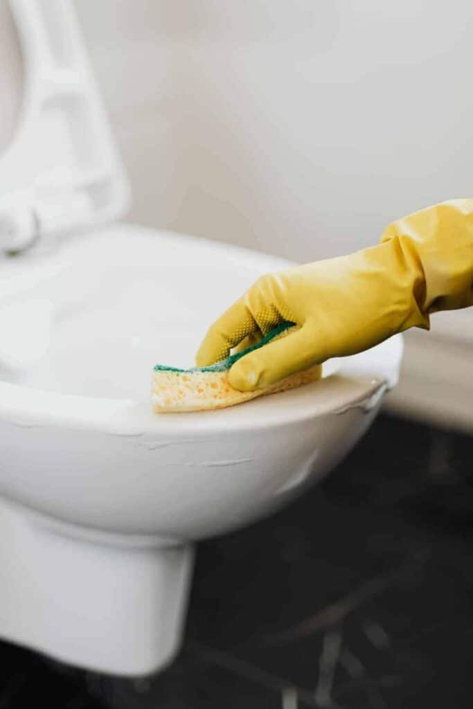 Wiping toilet clean with foaming toilet cleaner.